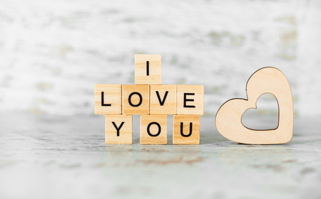 the phrase I love you wooden cubes and a wooden heart on a light wooden background Stock Photo