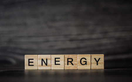 the word energy, consisting of light wooden square panels on a dark wooden background Stok Fotoğraf