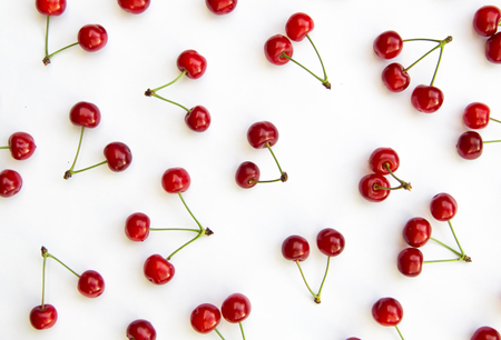 Cherries on white background isolated in chaotic manner as background