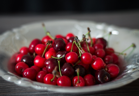 cherries in a metal plate on a dark wooden background