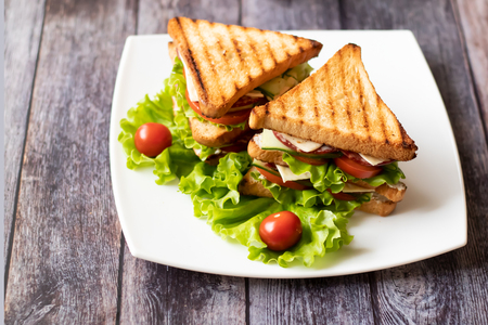 Sandwich with cheese, tomato, cucumber, sausage and salad on wooden background. Horizontal orientation Standard-Bild