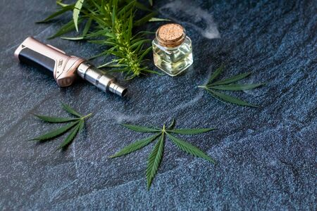Close-up Vaping Cannabis THC Oil Extract in Cartridge Isolated on Dark Background with Marijuana