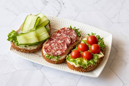 Fresh sandwiches with sausage, cheese, bacon, tomatoes, lettuce, cucumbers on a light background. Horizontal orientation