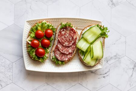 Fresh sandwiches with sausage, cheese, bacon, tomatoes, lettuce, cucumbers on a light background. Horizontal orientation Imagens