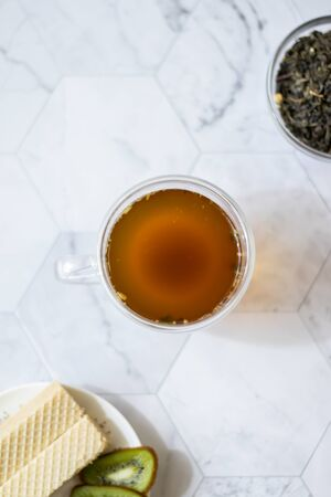 Green tea with jasmine in a transparent mug on a light background. Vertical orientation