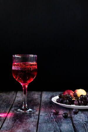 Vino rosado. Vino en un vaso cerca de frutas y uvas. Vino tradicional georgiano según tecnología antigua. Copie el espacio Primer plano y orientación vertical. Foto de archivo
