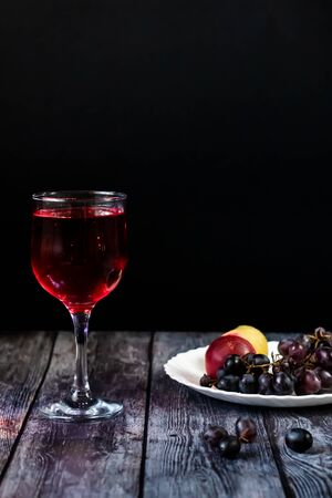 Pink wine. Wine in a glass near fruits and grapes. Traditional Georgian wine according to ancient technology. Copy space Close up and vertical orientation.