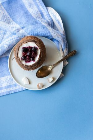 Berry dessert with yogurt in a cup of coconut on a blue background. Blackberries, raspberries, blueberries, black currants. Blue napkin