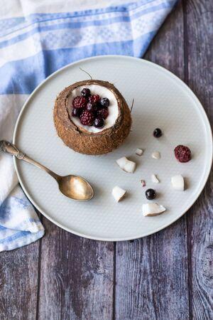 Berry dessert with yogurt in a cup of coconut on a wooden background. Blackberries, raspberries, blueberries, black currants. Banco de Imagens