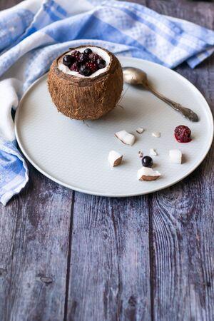 Berry dessert with yogurt in a cup of coconut on a wooden background. Blackberries, raspberries, blueberries, black currants. Blue napkin Banco de Imagens