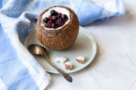 Berry dessert with yogurt in a cup of coconut on a light background. Blackberries, raspberries, blueberries, black currants. Blue napkin