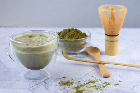 Matcha green latte tea with coconut milk. This latte is a tasty way to enjoy the energy and health benefits of a match. Matcha is a green tea leaf powder filled with antioxidants. Horizontal orientation Banco de Imagens