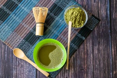 matcha of green tea in a bowl on a wooden surface. Top view, contains antioxidants, detox.