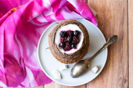 Berry dessert with yogurt in a coconut on a wooden background. Blackberries, raspberries, blueberries, black currants.