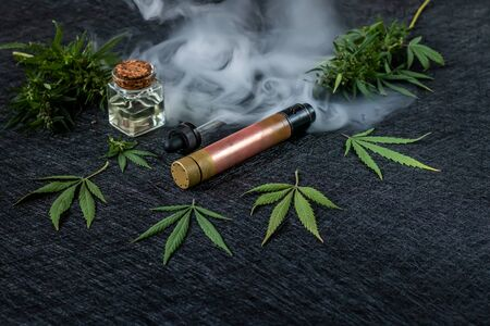 Cannabis liquid. Vape CBD or THC, Vaping Marijuana and Hemp. Against a Dark Background. Puffs of steam. Horizontal orientation