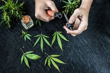 Cannabis liquid. Vape CBD or THC, Vaping Marijuana Leaves and Hemp. On a dark background. Puffs of smoke. Horizontal orientation Banco de Imagens