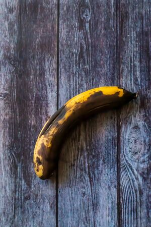 A spoiled rotten banana lies on a wooden surface. Rotten fruit
