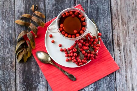 Hot healing tea, mountain ash tea. Applied with a lack of vitamins, anemia, metabolic disorders. Reduces the level of harmful cholesterol in the blood, strengthens blood vessels. healing drink on a wooden background with a red napkin