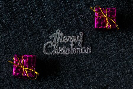 Merry Christmas lettering on a black background with gifts