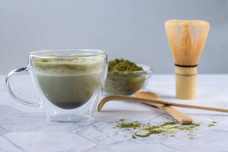 Matcha green latte tea with coconut milk. This latte is a tasty way to enjoy the energy and health benefits of a match. Matcha is a green tea leaf powder filled with antioxidants. Horizontal orientation Stock Photo
