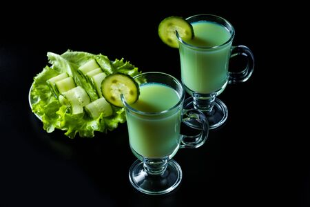 Kefir, Gemüse und Gurken-Smoothie, ein Sauermilchgetränk. Auf schwarzem Hintergrund.