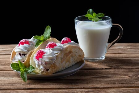 Kefir is decorated with a leaf of mint, a fermented drink. Air cake on a saucer. wood background Foto de archivo - 135469453