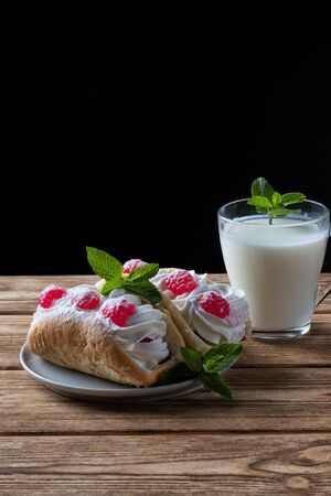 Kefir is decorated with a leaf of mint, a fermented drink. Air cake on a saucer. wood background Foto de archivo - 135469458