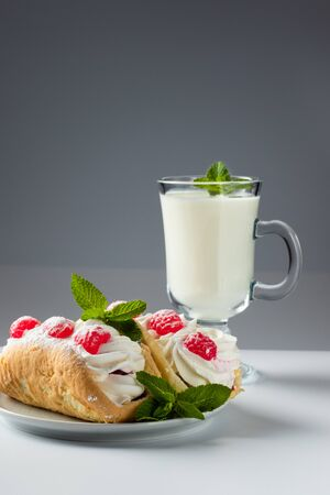 Kefir is decorated with a leaf of mint, a fermented drink. Air cake on a saucer on a white background Foto de archivo - 135469460