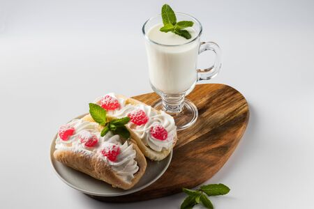 kefir is decorated with a leaf of mint, a fermented drink. Air cake on a saucer. Foto de archivo - 135469537