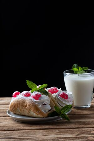 Kefir is decorated with a leaf of mint, a fermented drink. Air cake on a saucer. wood background Foto de archivo - 135469540