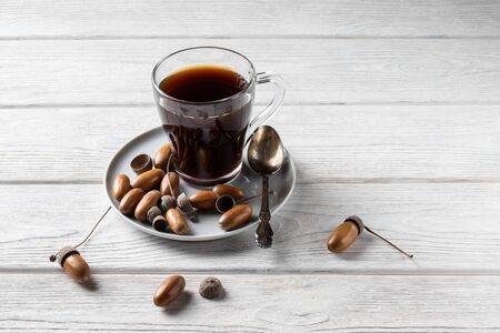 Acorn coffee in a glass is a tonic drink with a coffee flavor, rich color and pleasant aroma. On a white wooden background 版權商用圖片