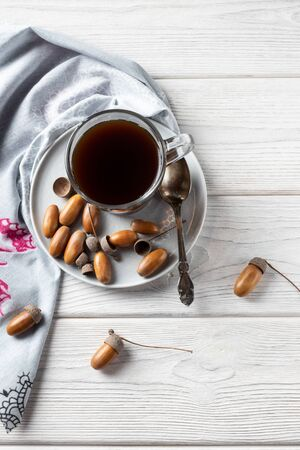 Hot coffee made from acorns in a glass with a napkin is a tonic drink with a coffee flavor, rich color and pleasant aroma. On a white wooden background 版權商用圖片 - 135469544