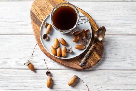 Acorn coffee in a glass is a tonic drink with a coffee flavor, rich color and pleasant aroma. On a white wooden background Stock fotó