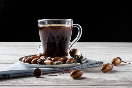 Acorn coffee is a tonic with a coffee flavor, rich color and pleasant aroma. On a white wooden background Фото со стока