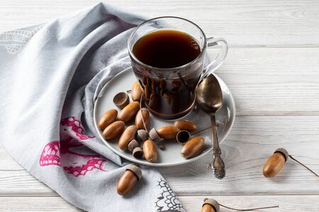 Hot coffee made from acorns in a glass is a tonic drink with a coffee flavor, rich color and pleasant aroma. On a white wooden background