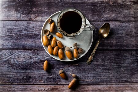 Acorn coffee is a tonic with a coffee flavor, rich color and pleasant aroma. On a dark wooden background Фото со стока