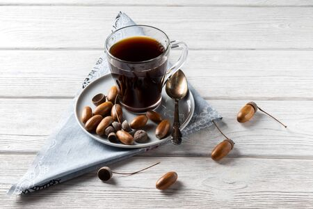 Acorn coffee in a glass is a tonic drink with a coffee flavor, rich color and pleasant aroma. On a white wooden background Фото со стока