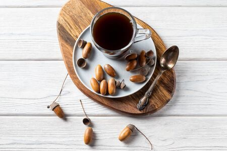 Acorn coffee is a tonic with a coffee flavor, rich color and pleasant aroma. On a white wooden background Zdjęcie Seryjne