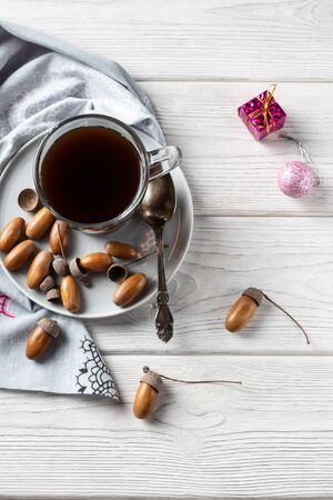 Hot coffee made from acorns in a glass with a napkin is a tonic drink with a coffee flavor, rich color and pleasant aroma. On a white wooden background. Christmas decorations