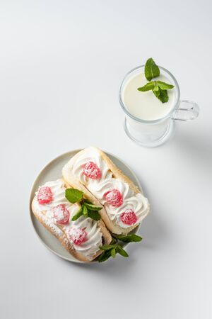 Kefir is decorated with a leaf of mint, a fermented drink. Air cake on a saucer on a white background