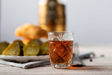on a wooden table is a glass of cognac, a snack of a piece of dark chocolate and a bottle of alcohol