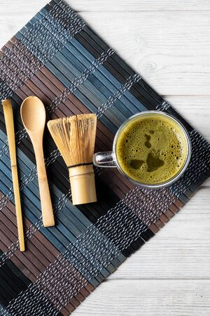 Green matcha tea drink and accessories on a white wooden background. Japanese tea ceremony concept.