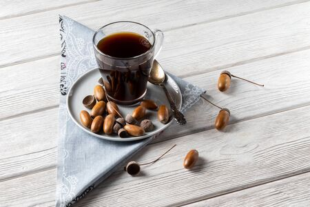 Hot coffee made from acorns in a glass with a napkin is a tonic drink with a coffee flavor, rich color and pleasant aroma. On a white wooden background