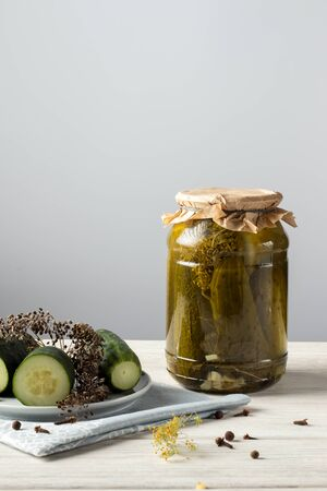 Homemade pickled cucumbers in a glass jar on a white wooden background