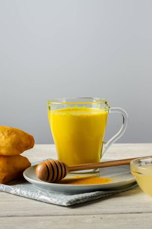 Golden milk with turmeric and honey, a traditional Indian drink on a white wooden background 写真素材