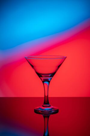 Martini glass on a colored background with reflection