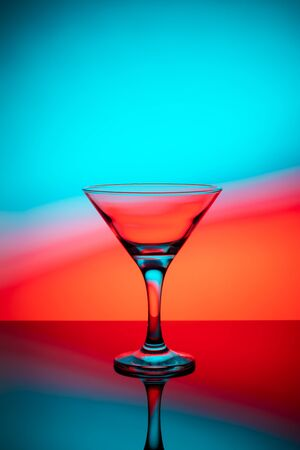 Martini glass on a colored  with reflection 写真素材