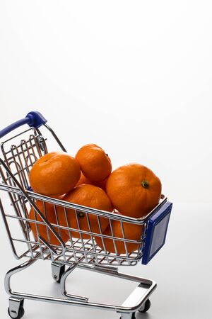 Trolley with tangerines on a white background 写真素材
