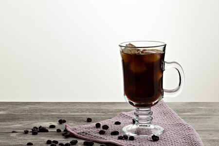 Iced coffee with ice, on wooden background