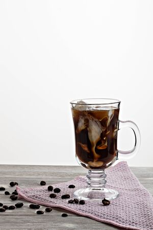 Cold coffee with ice and cream, on wooden background 写真素材